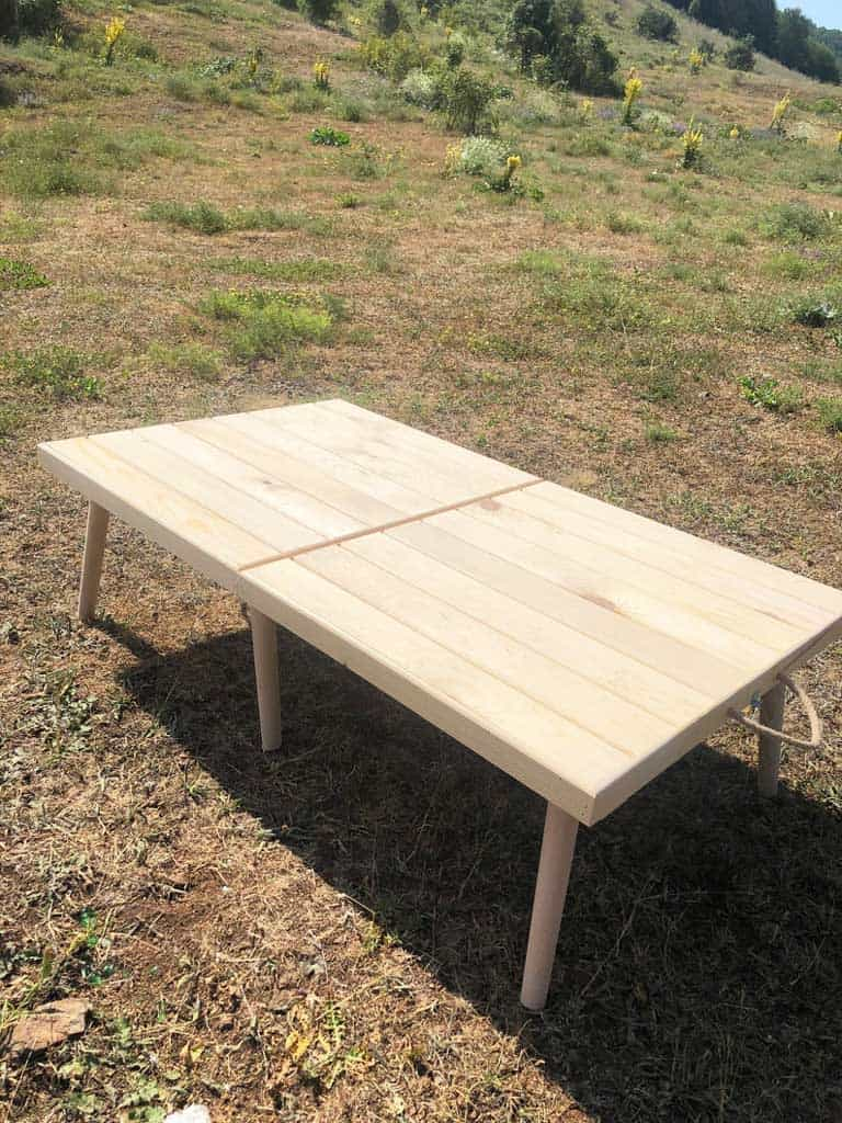 Foldable wooden picnic table set up outside on the grass.