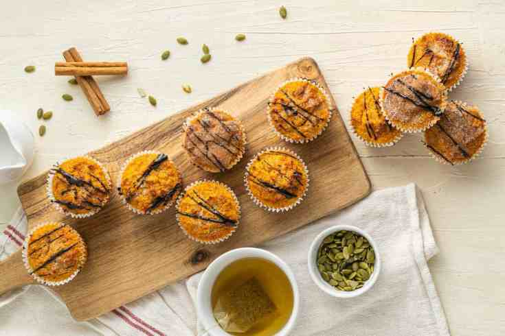 Keto pumpkin spice muffins on a wooden board with a cup of herbal tea.