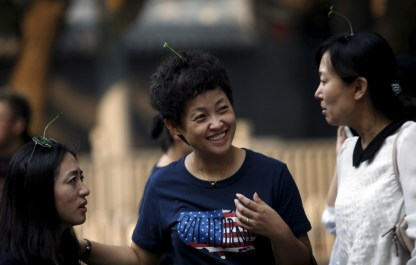 Women wearing sprouts-like hairpins chat on Nanluoguxiang street in Beijing