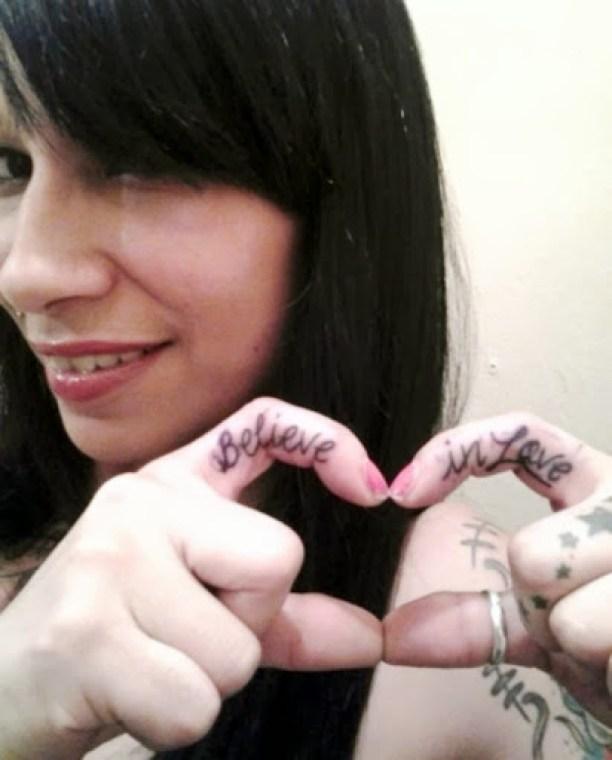 Believe In Love Black Ink Finger Tattoo For Smiling Girl