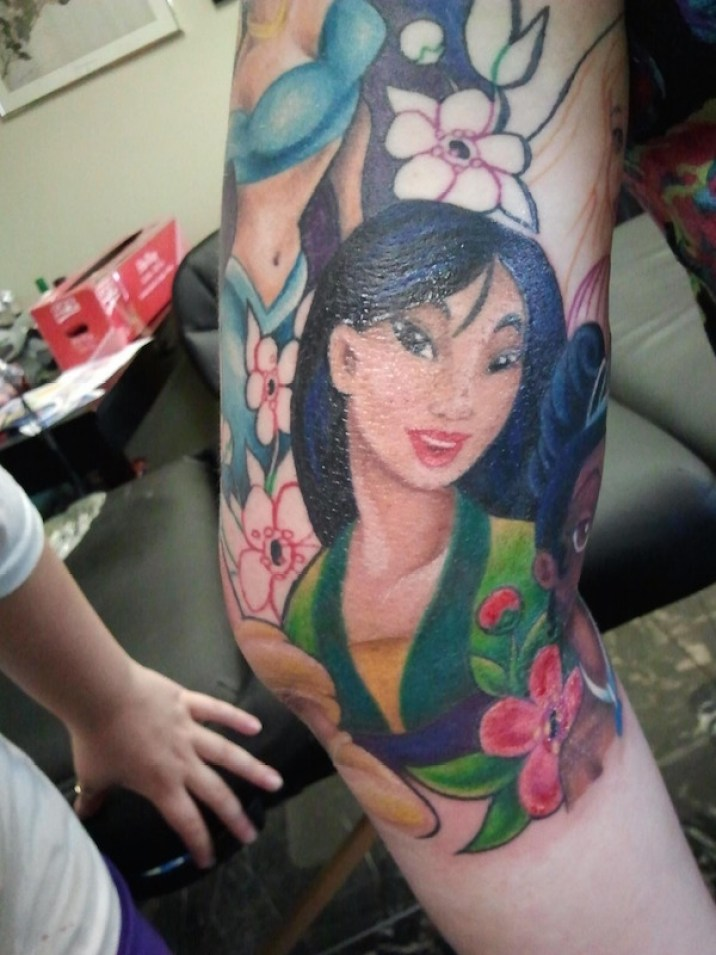 Lovely Colorful Animated Asian Girl Face Tattoo On Men Sleeve