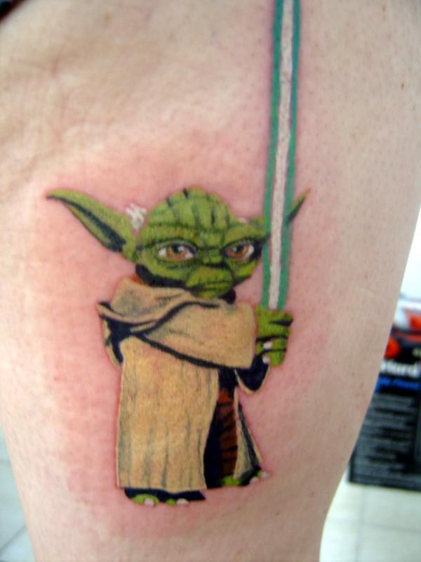 Wonderful Green Ink Animated Yoda With Sword Tattoo On Thigh