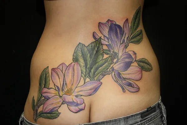 most incredible Magnolias tattoo on low back With colourful ink For Man And Woman