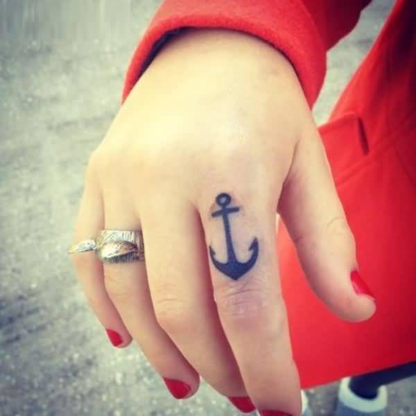 nice black color ink anchor tattoo on girl's finger made by expert