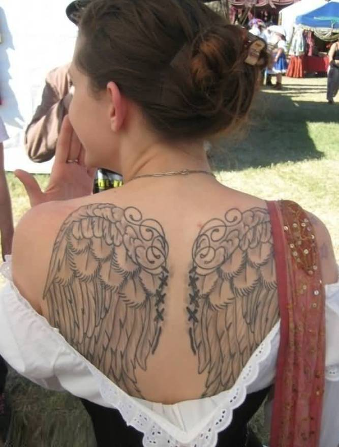 terrific black color ink angel wings on girl's full back side for female made by expert artist