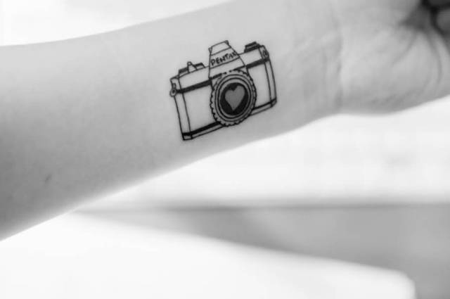 Beautiful Black Color Ink Heart Shutter Camera Tattoo On Wrist For Girls