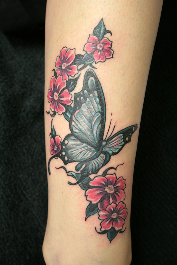 Maori Green Black And Red Color Ink Butterfly With Flowers Tattoo On Arm For Girls