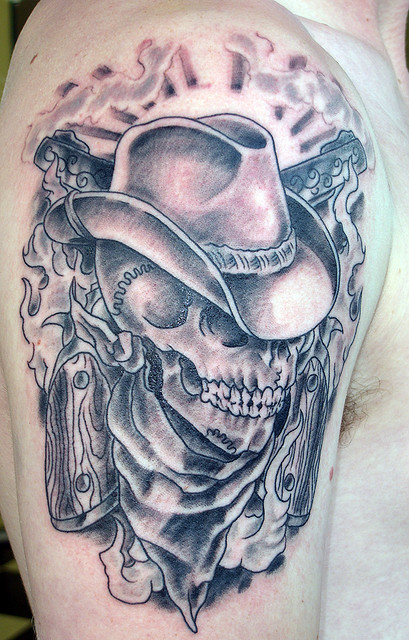 Marvelous Black And Red Color Ink Cowboy Skull With Crossing Revolvers Tattoo On Upper Arm For Boys