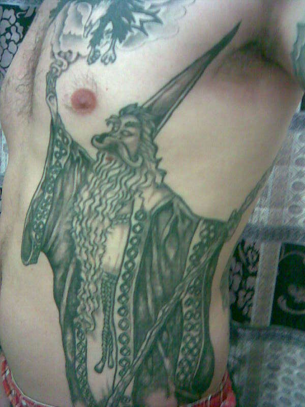 Nice Wizard WIth Long Beared Tattoo On Rib Side With Green Ink