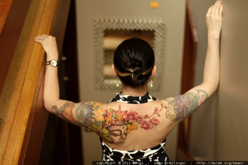 Passionate Green Blue Black And Red Color Ink Buddhist & Flowers Tattoo For Women On Back