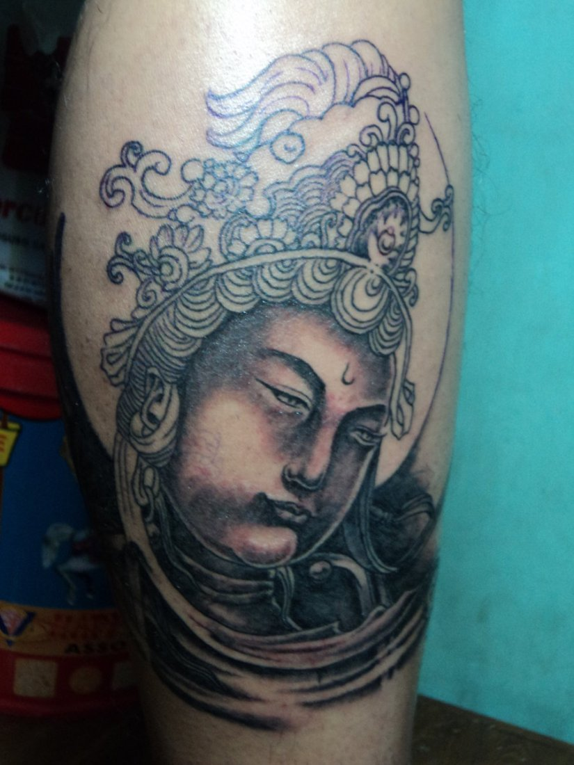Perfect Black And Red Color Ink Buddha Head Tattoo On Leg For Girls
