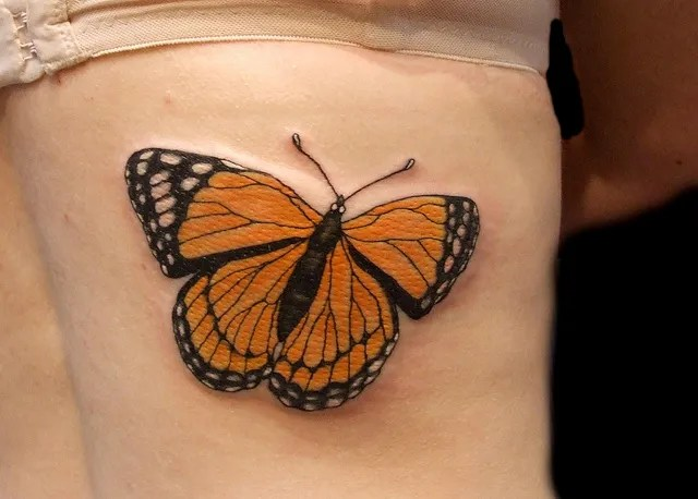 Sensation Orange And Black Color Ink Monarch Butterfly Tattoo Design On Rib For Girls