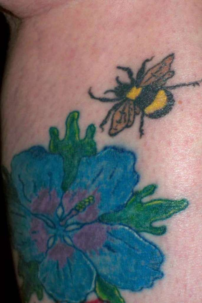 Stunning Blue Green Black And Yellow Color Ink Bumblebee Landing On Flower Tattoo For Girls On Leg