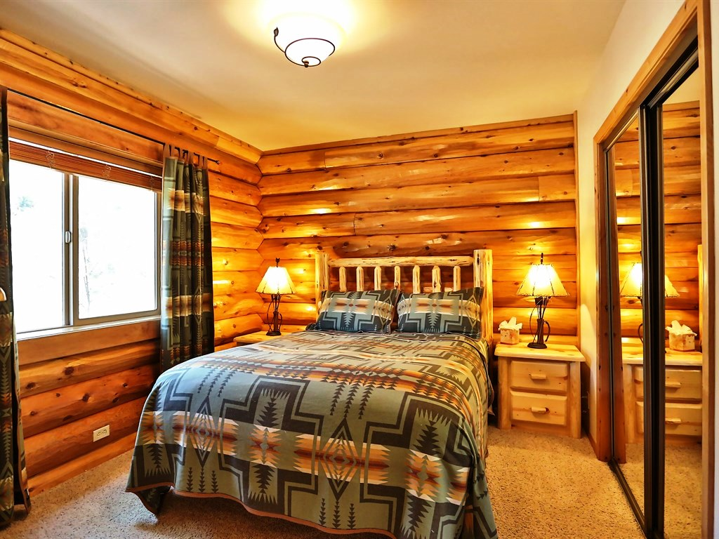 A beautiful bed with a wooden frame coupled with two rustic bedside tables.