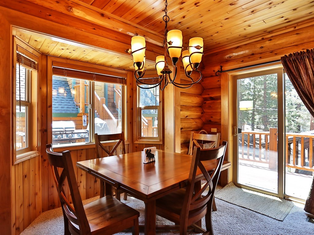 Beautiful wood table with rustic, overhead chandelier and access to patio.