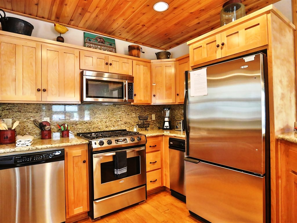 Stainless steel appliances coupled with golden wooden cabinetry and flooring make this kitchen a delightful space to prepare and eat food.
