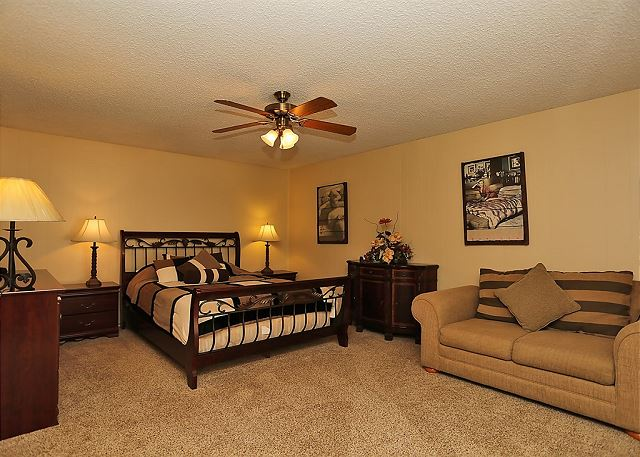 This master bedroom includes a comfy sofa and a queen size bed.