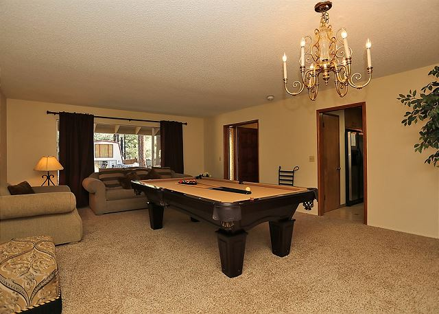 This room includes comfy seating, a beautiful chandelier and a pool table.