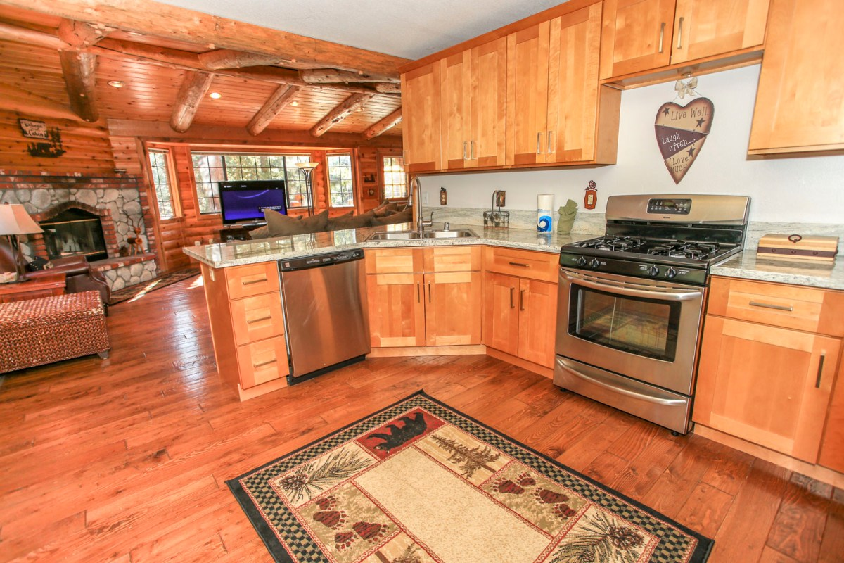 Wood finished cabinetry, stainless steel appliances and rustic decor give this kitchen a modern, cabin feel.
