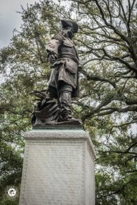 Bronzed statue of General Oglethorpe standing on palmetto leaves with sword at his side.
