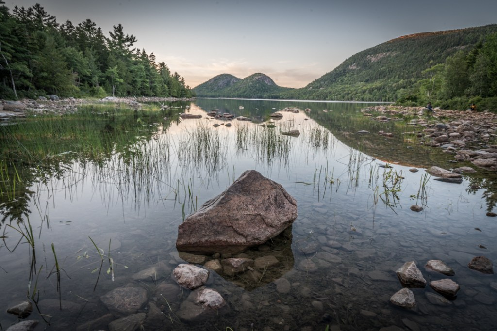 The clear waters of Jordan Pond in Acadia National Park reflect the sun and the rocks.