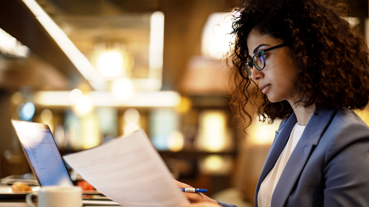 studious person in library holding papers in front of laptop