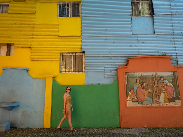 A girl walks in front of colourful walls at El Caminito, Buenos Aires, Argentina