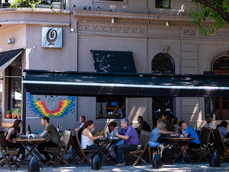 Locals enjoy drinks and food underneath a terrace on a busy street in Palermo, Buenos Aires, Argentina
