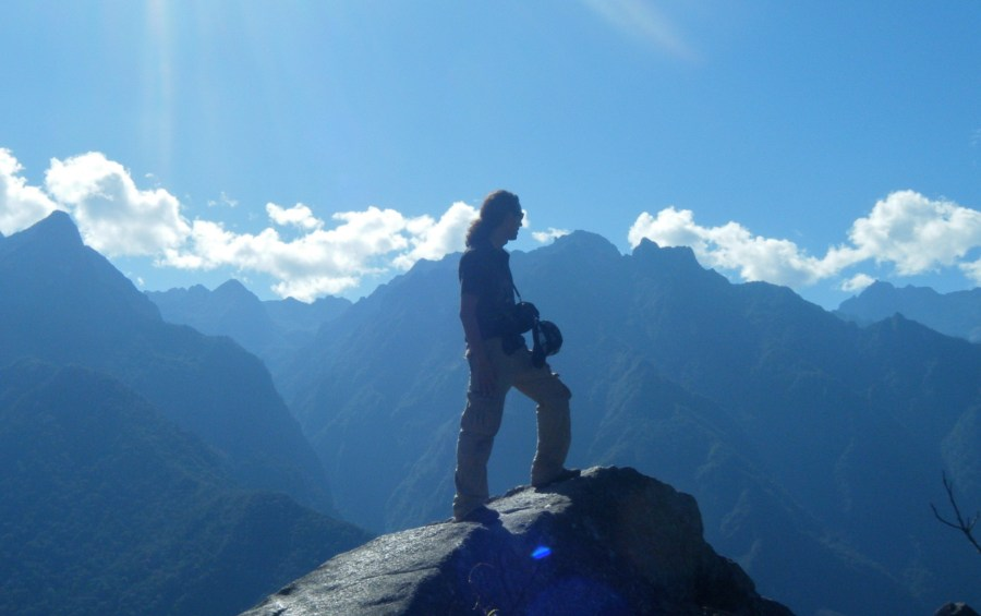 Inca Jungle Trail - Trekker on rock takes in cloud and mountain scenery.