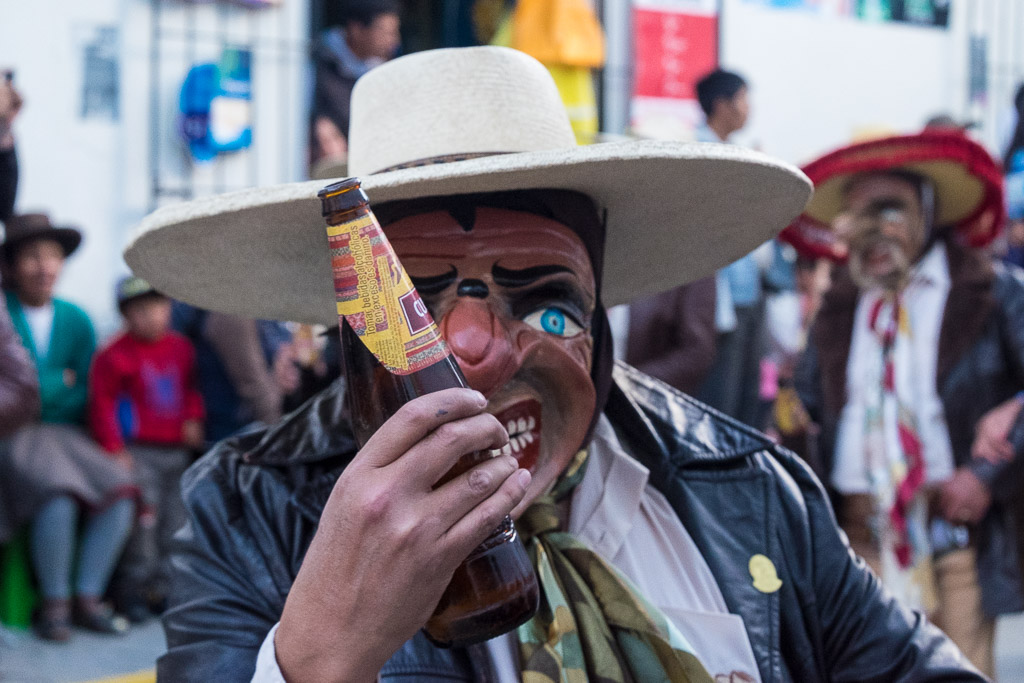 A masked Spanish conquistador holding a beer