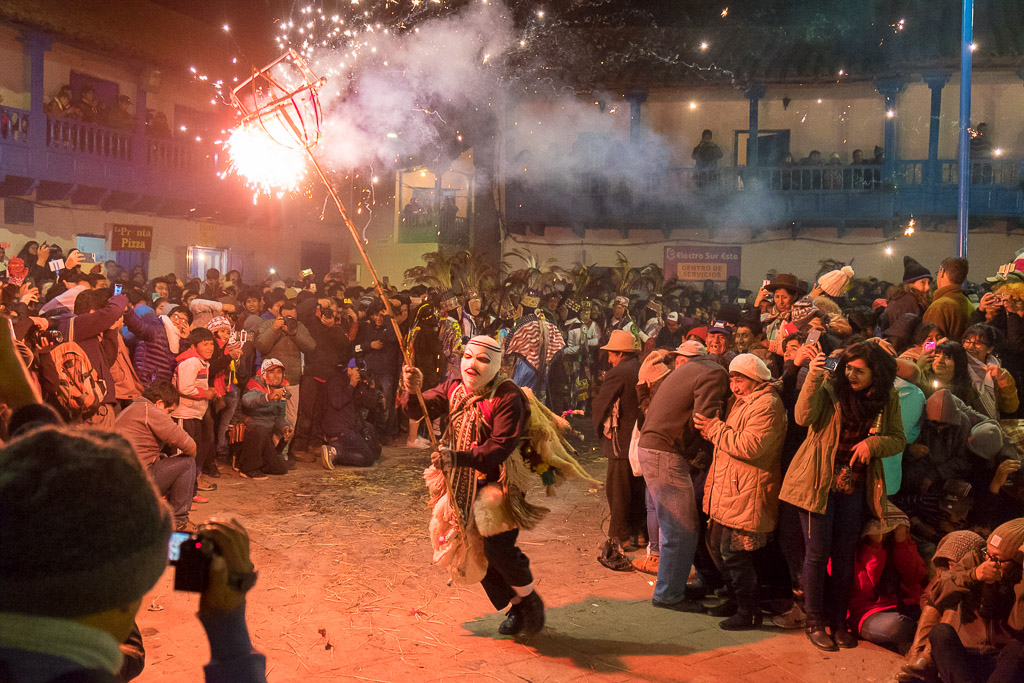 A masked character runs through the Virgin del Carmen Festival bearing fireworks