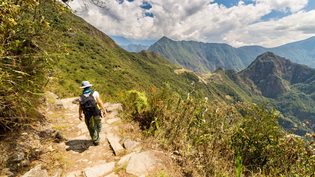 Backpacker exploring the steep Inca's footpaths of Machu Picchu, the most visited travel destination in Peru. Summer adventures in South America.