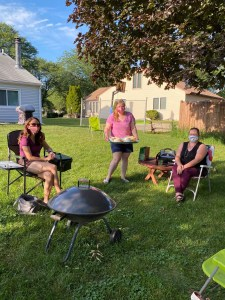 3 women in yard 1 servng food to the otehr 2