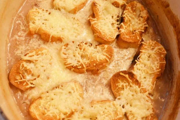 grilowane kawalki bagietki, z roztopionym , zoltym serem polozone na zupie cebulowej
