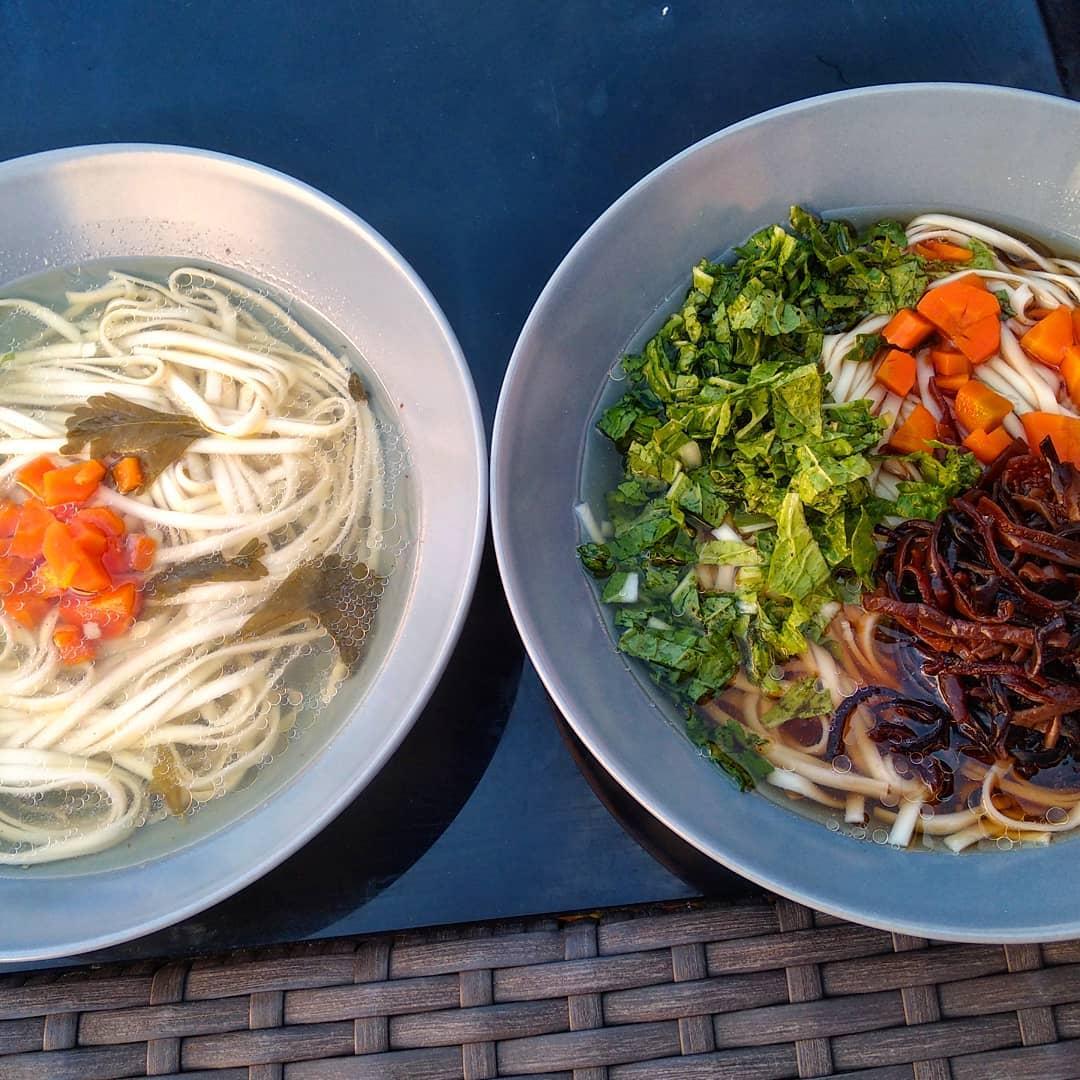 dwa talerze z rosolem, jeden z makaronem, drugi z kausta, grzybami i pokrojona w kostke marchewka