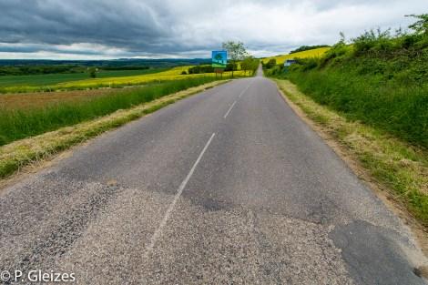"""Limite departementale ancienne frontiere -----------------  Après la défaite, l'accord de paix signé à Versailles le 26 février 1871 imposa l'annexion de l'Alsace-Moselle et une nouvelle frontière entre la France et l'Allemagne. Celle-ci courait du Luxembourg à la Suisse en bouleversant les pourtours des départements de la Moselle, de la Meurthe, des Vosges et du Haut-Rhin. En Lorraine, cette ancienne frontière perdure aujourd'hui, car le département actuel de la Meurthe-et-Moselle a conservé son exact tracé. L'entretien des routes départementales incombant aux Conseils Généraux, les goudrons de revêtement routier changent souvent de couleur quand l'on passe d'un département à l'autre. Deux guerres mondiales n'auront donc pas fait disparaitre ces lignes sur la chaussée. Plus de quatre mille bornes marquées d'un numéro et des lettres D et F ont été positionnées pour jalonner la nouvelle frontière de 1871. Aujourd'hui, certaines sont toujours visibles au bord des fossés. Les lettres D (Deutschland) ont presque toutes été martelées afin de les rendre illisibles. Entre 1871 et 1945, les Alsaciens-Mosellans ont changé cinq fois de nationalités. Cela explique que sur leurs monuments aux morts, à de rares exceptions, l'on n'y lit pas l'épitaphe """"Morts pour la France"""" mais plutôt """"A nos morts"""". Comment, en effet, commémorer le souvenir de ces hommes combattant pour l'armée allemande ?"""