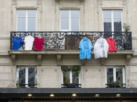 """In this picture taken on November 27, 2015 T-shirts and coats hang on a balcony in Paris, in arrangements to re-create the tri-colours of the French national flag in memory of the 130 victims of the November 13, 2015 coordinated terror attacks in Paris claimed by the Islamic State group (IS). A solemn ceremony was held for the victims of the Paris attacks, with President Francois Hollande vowing that France would respond to the """"army of fanatics"""" with more songs, concerts and shows. """"We will not give in either to fear or to hate,"""" said Hollande in the courtyard of the Invalides buildings in central Paris, speaking to 2,000 dignitaries and those injured in the violence. AFP PHOTO/ ALAIN JOCARD / AFP / ALAIN JOCARD"""