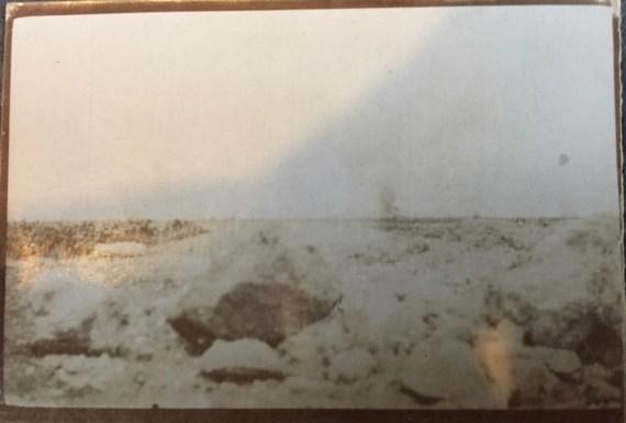 La photo semble prise d'une tranchée, au ras du sol, montrant une explosion dans le lointain