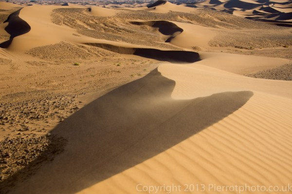 Wind blowing the sand off the top of sand dunes in the Sahara desert, Morocco