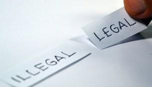"""Zettel mit den Worten """"legal"""" und """"illegal"""" auf dem Tisch."""
