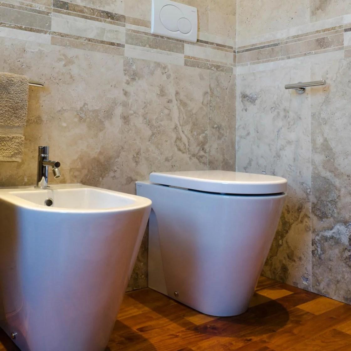 Bagno con rivestimento in travertino e pavimento in legno - Rivestimento bagno legno ...