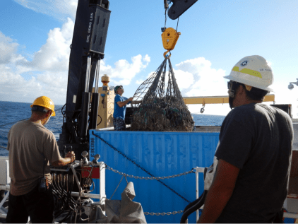 NOAA Ship Oscar Elton Sette crew members unloading one of many cargo nets full of derelict fishing gear. In six days of operations the marine debris team removed an astonishing 14,055 kg (30,985 lbs.) of net from the shallow coral reefs of Maro.