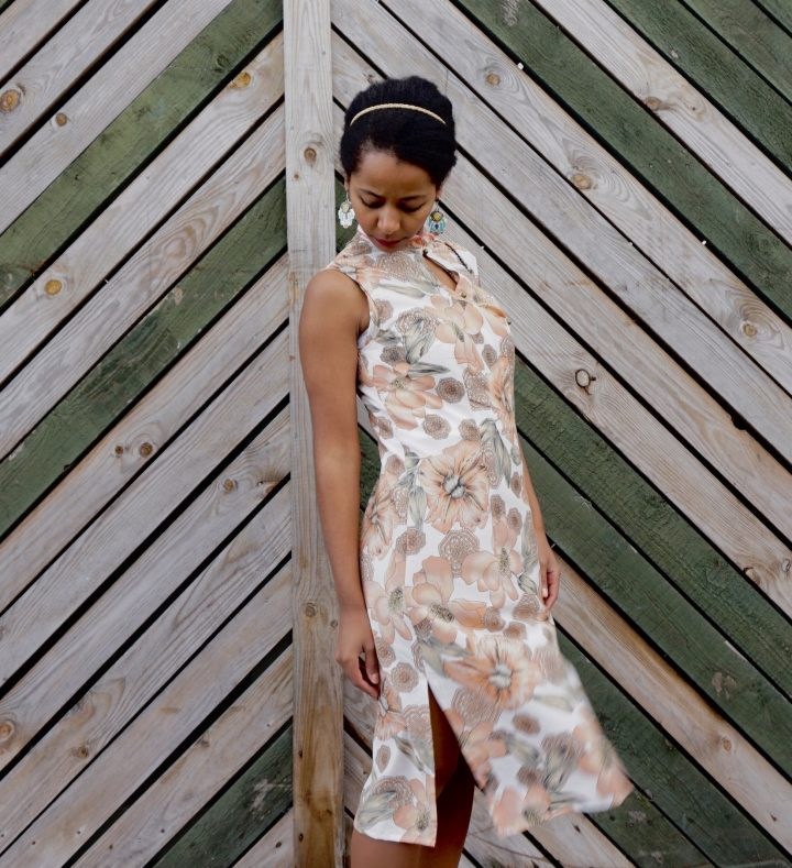 Megan is standing against a wooden fence. She is wearing her handmade qipao. The fabric has a floral print. Megan is looking down at the ground.