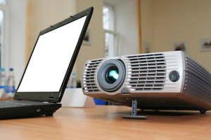 Laptop with computer projector on table