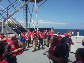 Fire and Abandon Ship Drill. All crew members wearing life jackets, preparing to abandon ship in case of such an emergency takes place.