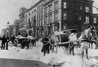Men shovel snow into horse drawn carts on the streets of New York - ca. 1900. Image © CORBIS