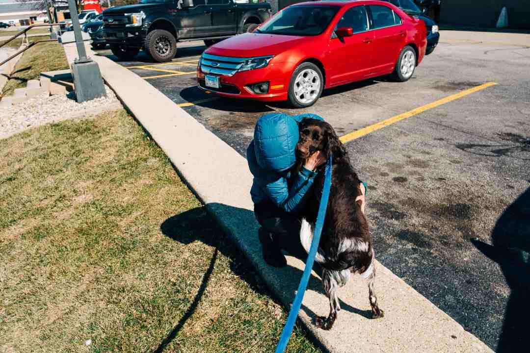 woman hugging dog in parking lot