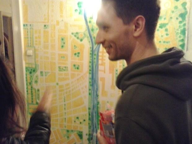Gaul Miklós a várostérképe alatt. A falon kis piros pöttyel mindenki bejelölheti a saját helyét
