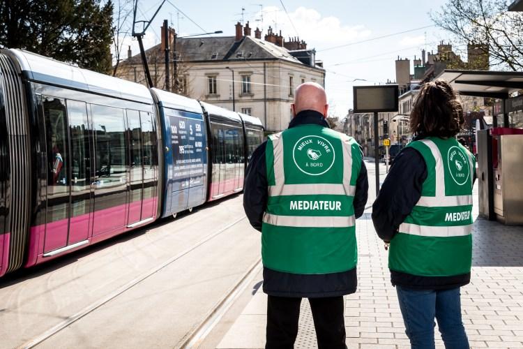 Deux médiateurs sociaux de Pimms Médiation Dijon sur le quai du tramway. Un tram passe sur la voie opposée.