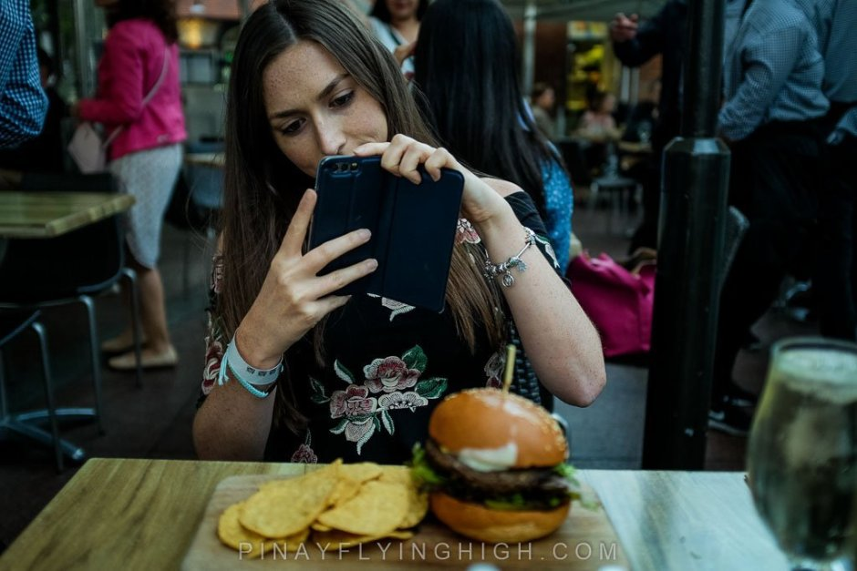 Girl taking photo of a burger.